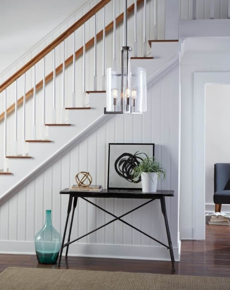 Farmhouse entryway showcases white staircase clad with beadboard and wood treads lighted by a chic pendant that hung over a black console table.