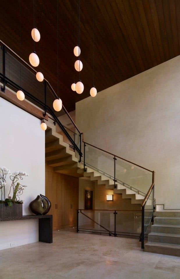 Glass globe pendants illuminate this spacious foyer with concrete staircase framed with glass railing and wooden handrail.
