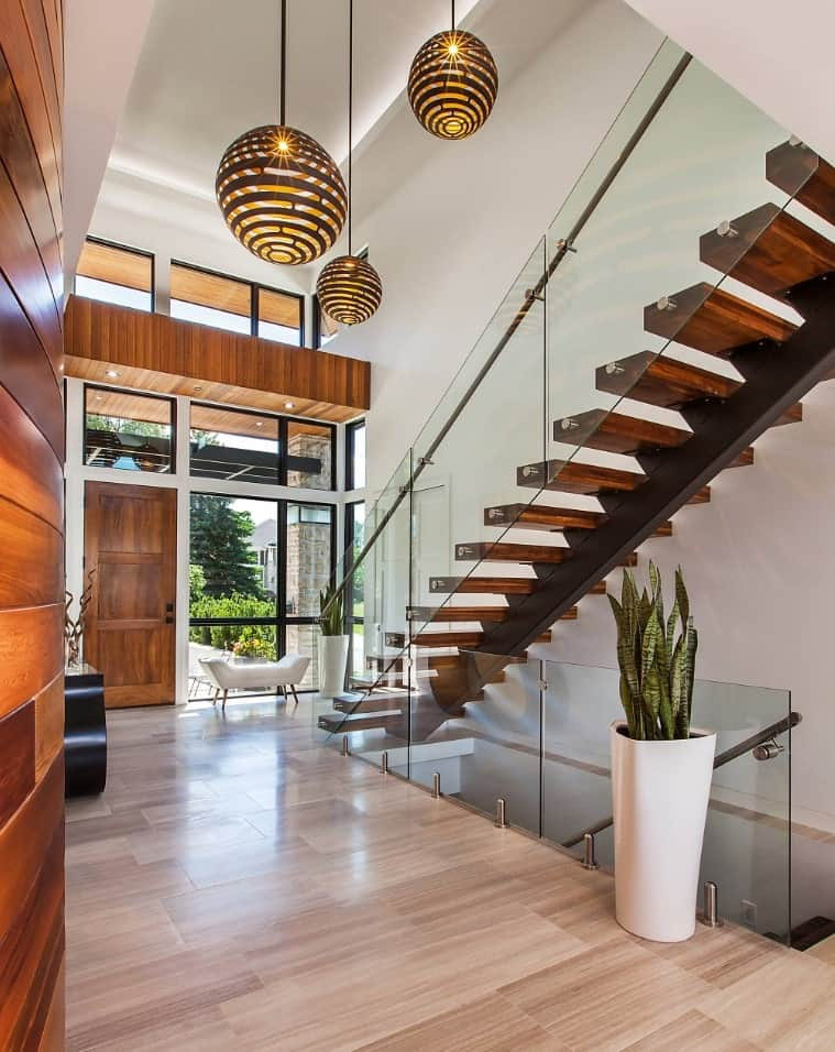 The contemporary entryway features a white sleek bench that faces the modern staircase. It is illuminated by oversized ball pendants that hung from the tray ceiling.