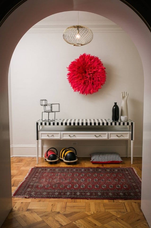 Eclectic entryway styled with a gorgeous red floral wall decor mounted above the striped console table. It has hardwood flooring topped with a vintage rug.