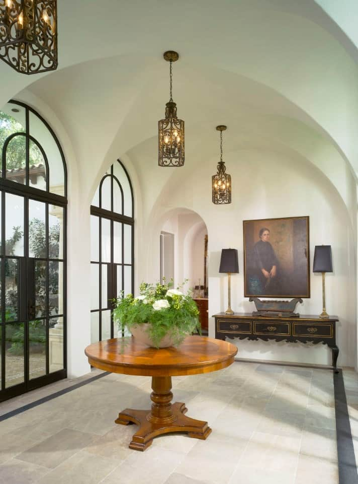 Ornate wrought iron pendants hang from the arched ceiling and illuminate this hallway. It has a round center table and dark wood console table accented by a lovely portrait.