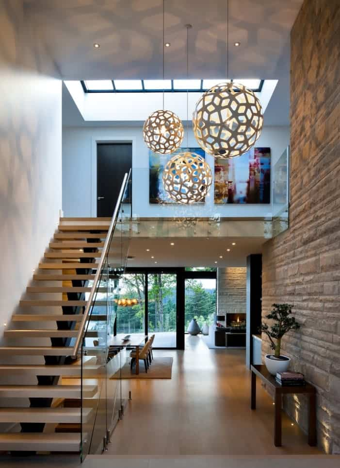 Contemporary foyer with a stone brick wall and modern staircase lighted by oversized ball pendants.