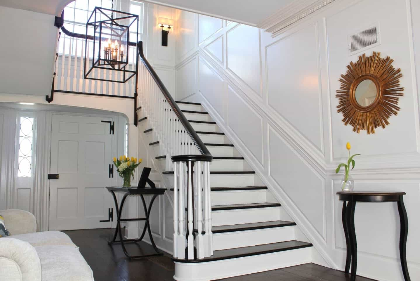 Traditional entryway showcases a staircase fixed to the white wall with full wainscoting and illuminated by a sconce and caged pendant light. It is decorated with a sunburst mirror mounted above the dark wood console table.