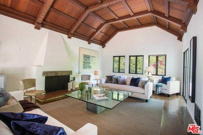 Vaulted ceiling with exposed wood beams covered this white living room. It has matching sofas and chairs with a glass top center table facing the fireplace.