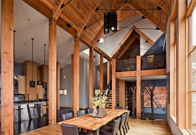 Farmhouse dining area surrounded by natural wood columns and covered with a wood plank cathedral ceiling.
