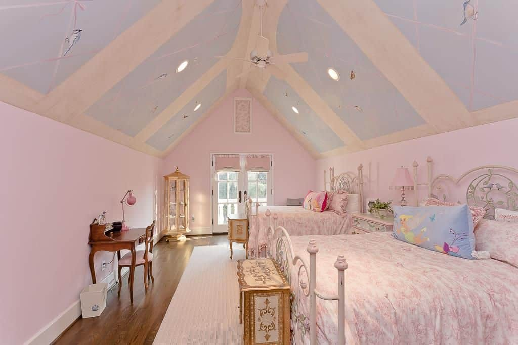 Charming pink girls bedroom showcases metal beds dressed in floral bedding and a blue and white cathedral ceiling painted with ribbons and birds.