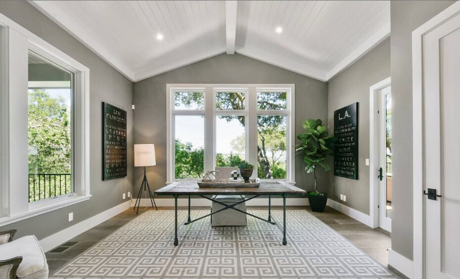 Gray office room accented with white linings and shiplap cathedral ceiling showcases a wooden table paired with an upholstered chair that sits on a geometric rug.