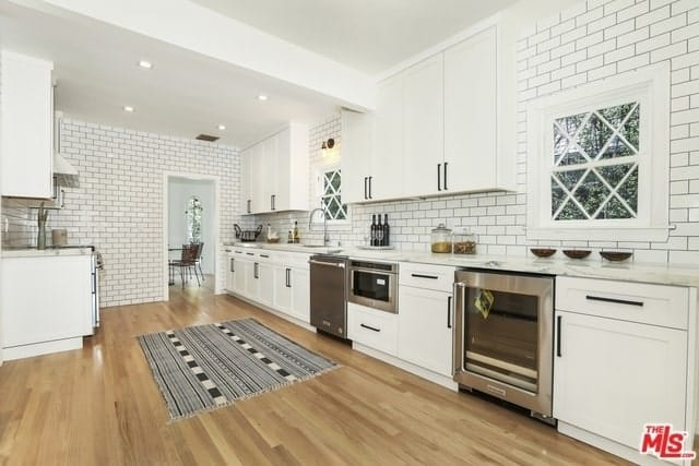 This large kitchen has white tiles on its walls that are arranged in a brick wall pattern and has black grout to emphasize the lines. This pairs well with the white shaker cabinets and drawers that house the stainless steel appliances.