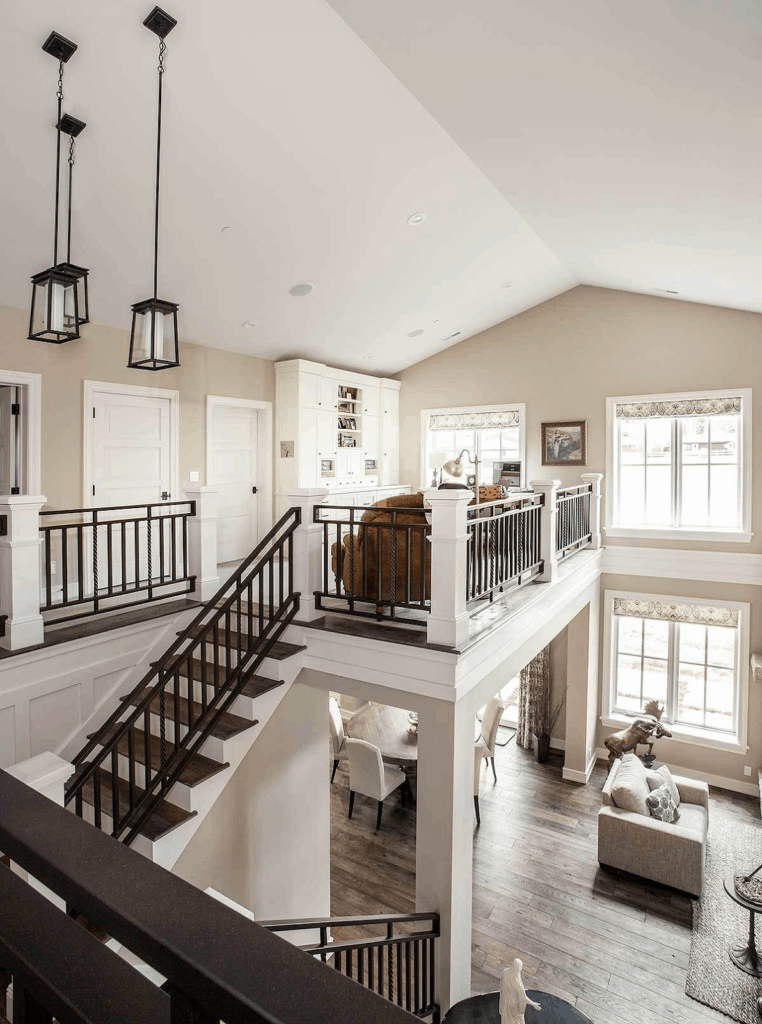 Loft style house with dark wood plank flooring and white cathedral ceiling mounted with recessed lights and industrial pendants.
