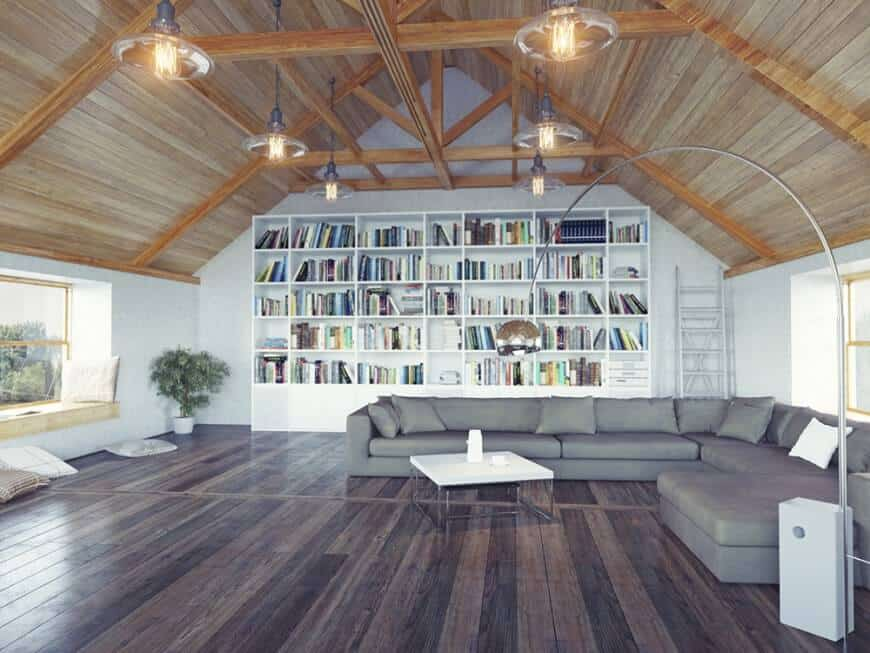 Loft living room features an L-shaped gray sectional paired with a white coffee table and a window seat nook. It has dark hardwood flooring and wood cathedral ceiling with hanging glass pendants.