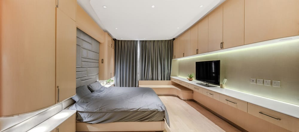 This is a contemporary primary bedroom dominated by the light wooden tones on the hardwood flooring, walls, cabinets and the built-in desk and bench. These are then complemented by the gray elements.
