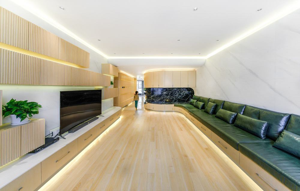 This contemporary living room has light wooden tones on the floor and wall accents complemented by the modern lighting and the green cushions of the built-in sofa.