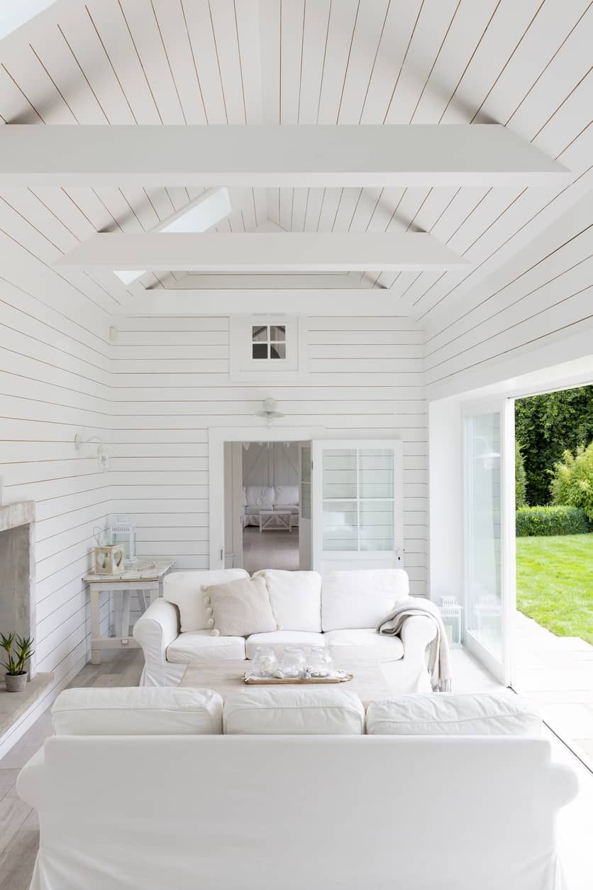 White shiplap living room showcases facing white sectional sofas and a sliding glass door that opens to the luscious green yard.