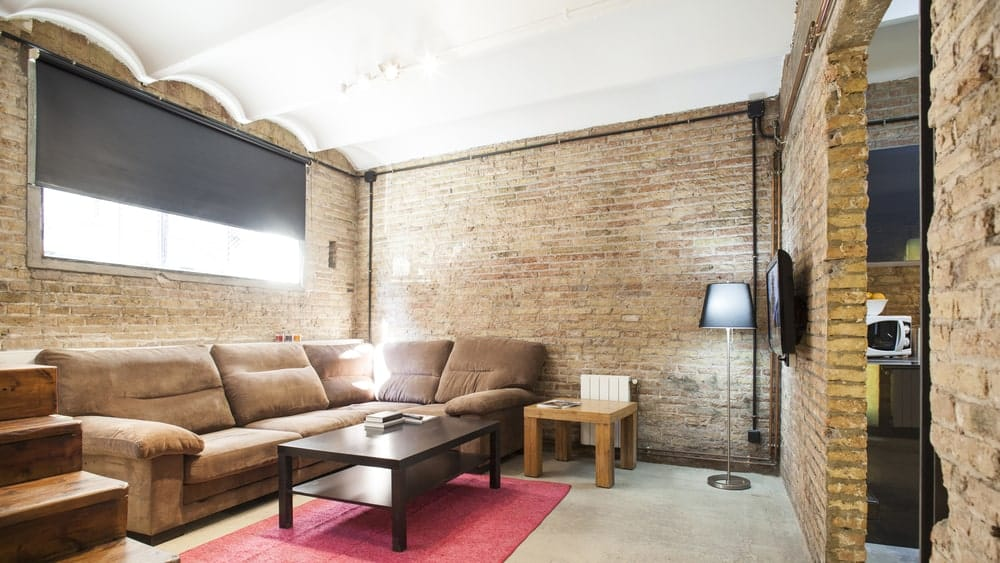 Industrial living room surrounded with brick walls that are lined with electrical pipes. It has a brown velvet sectional and wooden coffee table on a red rug.