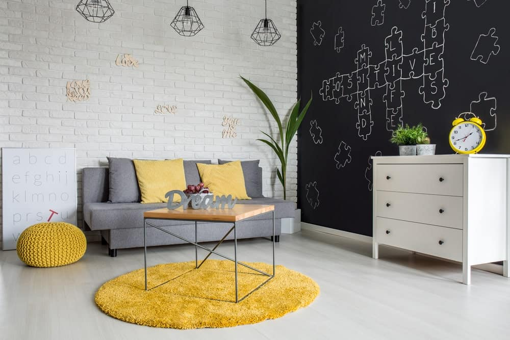Charming living room showcases a chalkboard and white brick walls. It is lighted by geometric pendants that hung over a gray couch accented with yellow pillows that complement with the knitted ottoman and round rug.