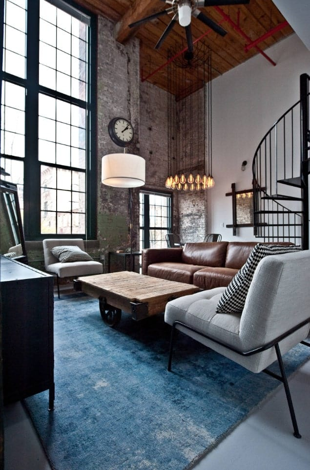 A floor lamp illuminates this living room along with industrial pendant lights that hung from a wood plank ceiling.