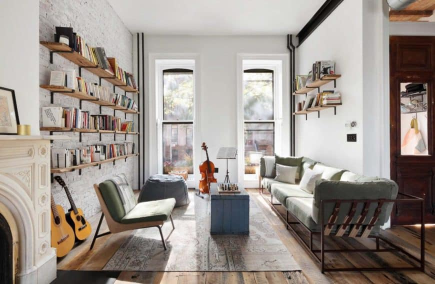 Bright living room showcases floating wood shelves topped with books. It includes a wood framed sectional and green chair with a blue distressed wood coffee table.