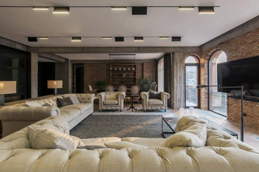 Magnificent living room furnished with beige tufted sofas and chairs along with a metal coffee table lighted by a floor lamp. It has a white ceiling lined with linear track lights.
