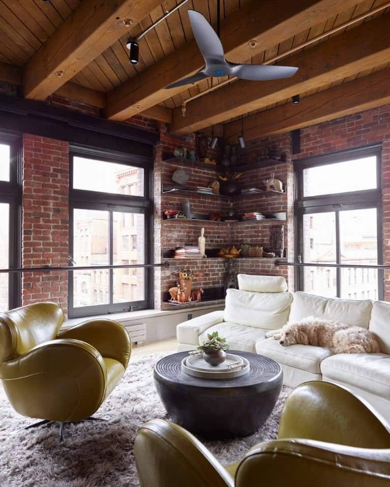 Living room with red brick walls fitted with glass windows that are framed with black metal rods. It has white sectional and yellow wingback chairs along with a round coffee table topped with a floral centerpiece.