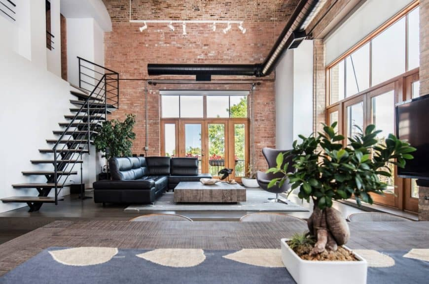 Fresh living room features a modern staircase across a black L-shaped leather sofa that complements with the large pipe fixed to the brick wall.