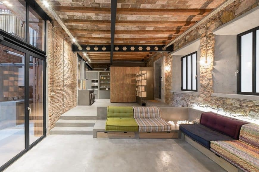 Marvelous living room boasts a concrete sofa fitted with wooden storages and multi-colored cushions. It has stone brick walls lighted by sconces and strip lights.