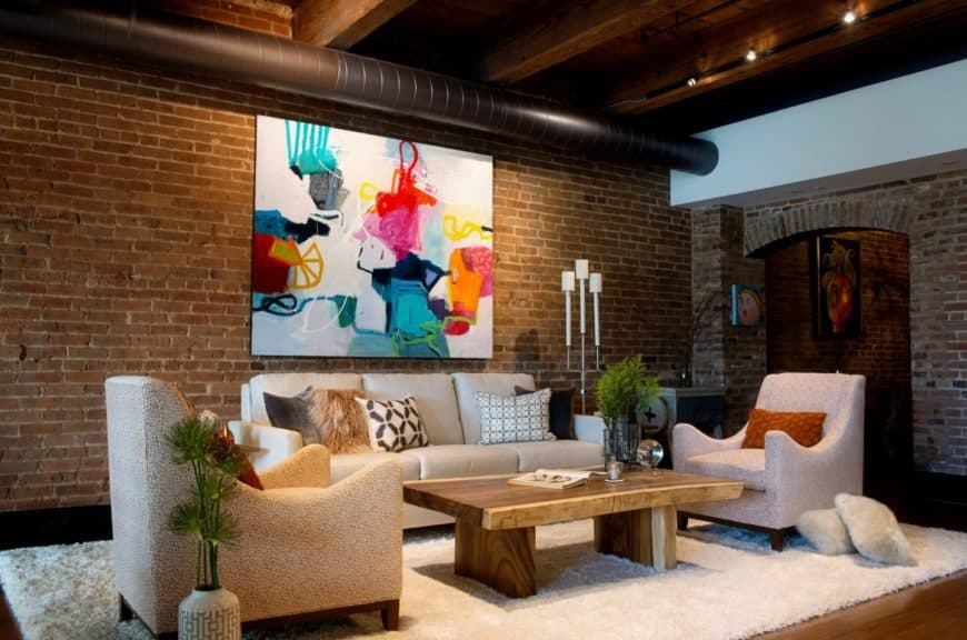 Fabulous living room boasts a colorful artwork mounted on the brick wall lined with a huge pipe. It has a beige sectional and armchairs paired with a wooden coffee table that sits on a shaggy rug.
