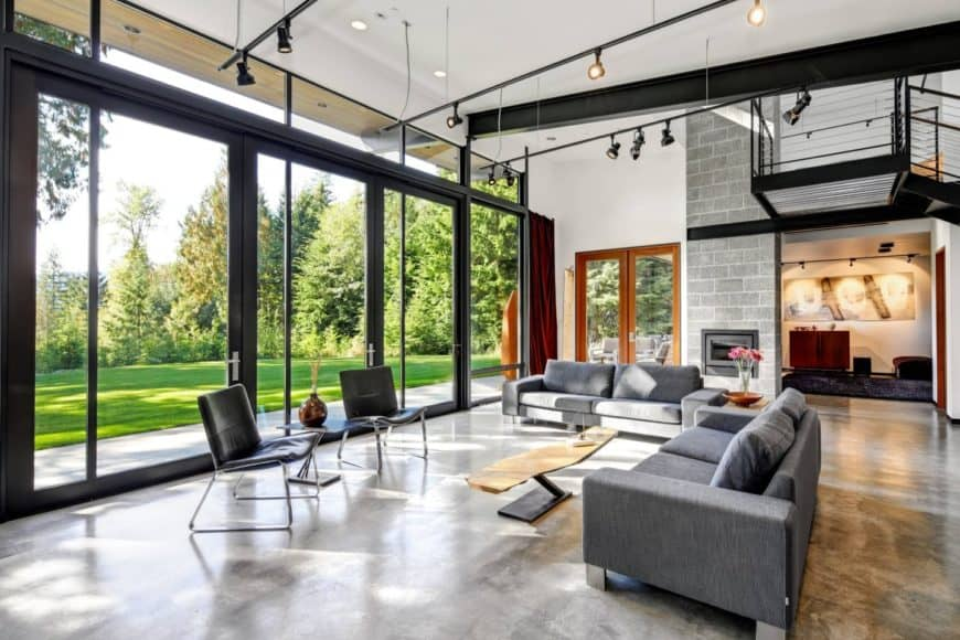 Expansive living room showcases a panoramic window overlooking the lush green outdoor view. It has concrete flooring and white ceiling with hanging track lights.