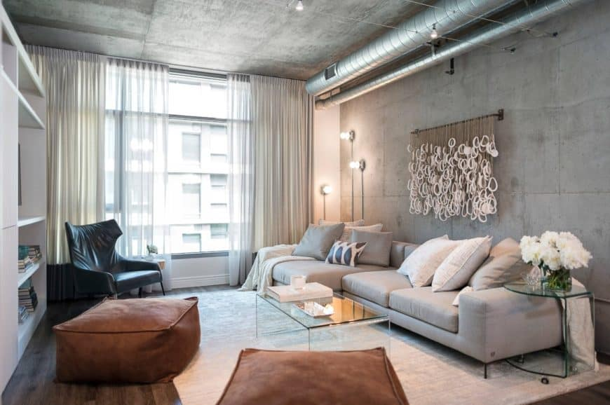 Industrial living room decorated with pipe lights and a unique wall art tied to a black steel rod over a gray sectional filled with neutral pillows and throw blankets.