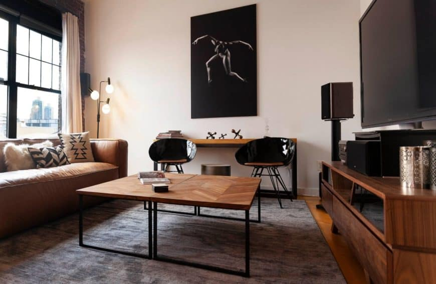 Industrial living room showcases a human canvas wall art mounted above the wooden console table topped with decorative iron jacks. A pair of glossy black stools and herringbone coffee tables sit in front of it.