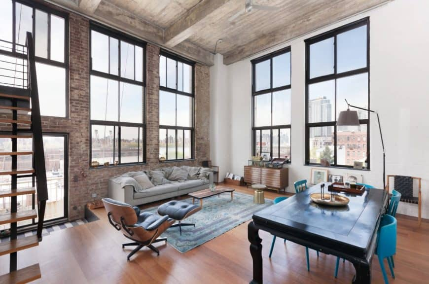 Bright living room surrounded with metal framed glass windows fitted on the white and brick walls. It has a gray sofa facing the black table with blue chairs.