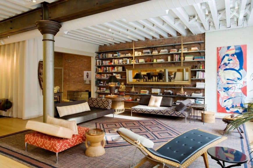 An open living room framed with wood beams and a metal column. It has a rectangular gold mirror fixed on the bookshelf.
