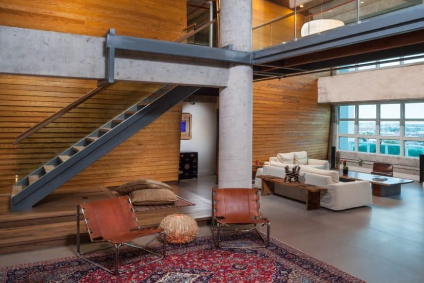 The expansive living room offers wood plank walls and two sitting areas. There are pillows and a striped rug underneath the staircase where you can also sit comfortably.