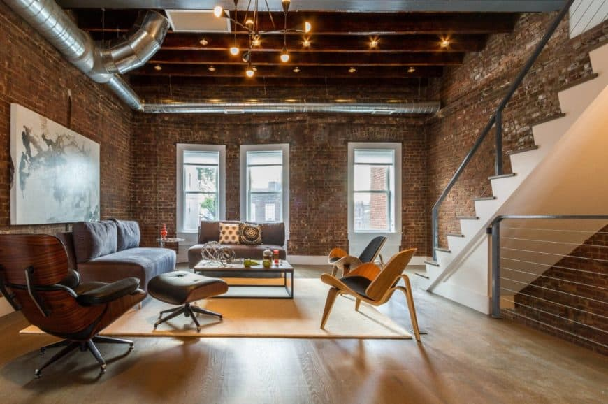 The warm living room features brick walls with exposed metal pipes and wood beam ceiling fitted with track lights.