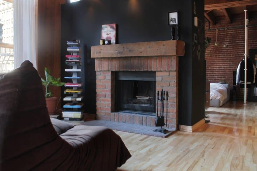 Industrial living room features a book rack next to a brick fireplace with a wooden mantel topped with decors and fixed to the black wall.