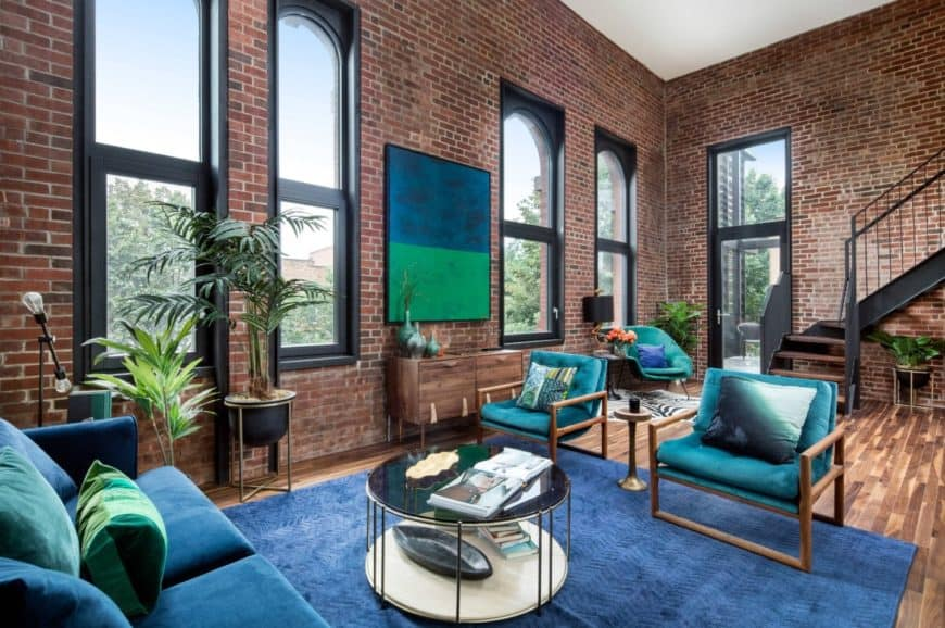 Gorgeous living room showcases a blue and green canvas wall art mounted on the brick wall complementing the sofa set and chevron area rug.