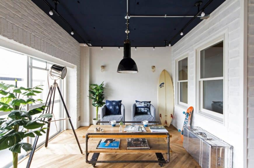 Fresh living room features herringbone flooring and deep blue ceiling surrounded with track lights. It is illuminated by an oversized black pendant and tripod floor lamp.