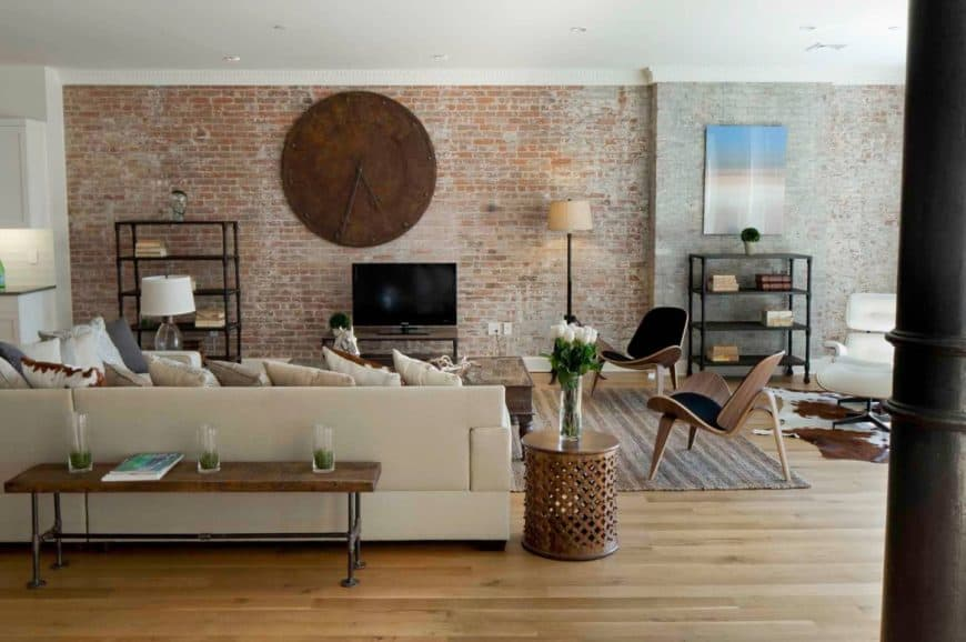 Industrial living room designed with wall art and an oversized rustic clock mounted on the brick wall. It has black wooden chairs and an L-shaped sofa lined with a wooden table.