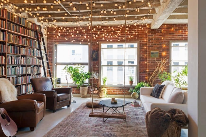 Light bulb string lights illuminate this living room with bookshelves framed with a metal rail and ladder.
