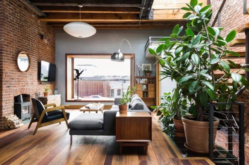 Cozy living room accented with indoor plants that create a refreshing ambiance to the space. It has wood plank flooring and brick wall mounted with television and round mirror.