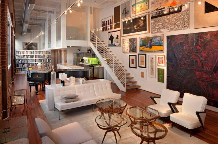 Gorgeous living room decorated with lovely wall arts and track lights fixed to the ceiling beams. It has a white tufted sofa and chairs paired with glass top coffee tables of different styles.