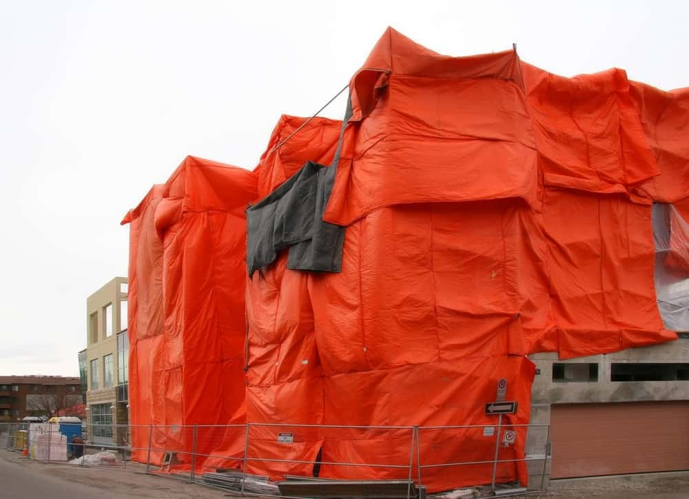 Building covered in orange insulated tarp.