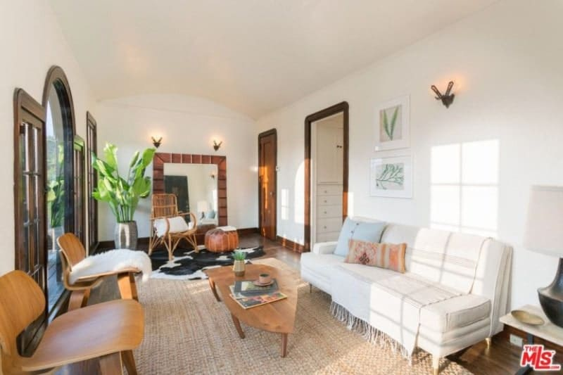 Bright living room offers a white sofa beautifully contrasted by wooden coffee tables and chairs. It includes an indoor plant that adds life to the room.