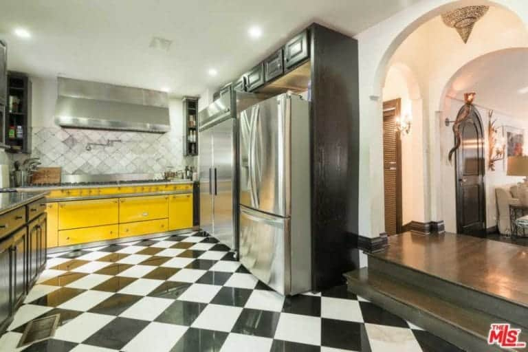 An arched entryway leads to this charming kitchen. The bright and cheerful yellow tone of the large stove-top oven serves as the highlight of this kitchen that has a checkered black white flooring that complements the stainless steel appliances.