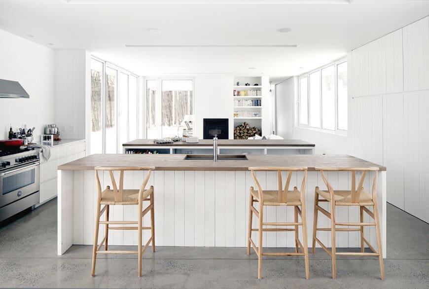 White kitchen with beadboard cabinetry and double breakfast island fitted with a sink and built-in storage. It has a black fireplace next to the open shelving filled with dinnerware and firewood.