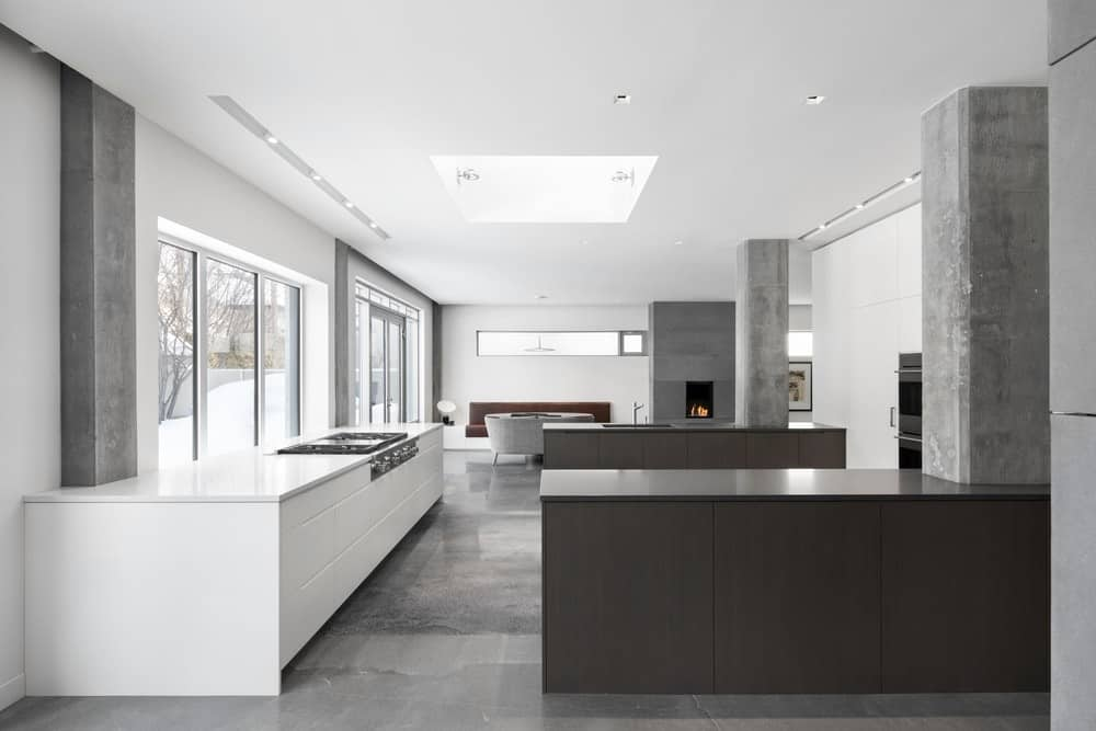 Sleek kitchen with glass windows and a skylight fitted on the white ceiling. It has white and dark wood counters along with a fireplace at the far end fixed on the concrete pillar.