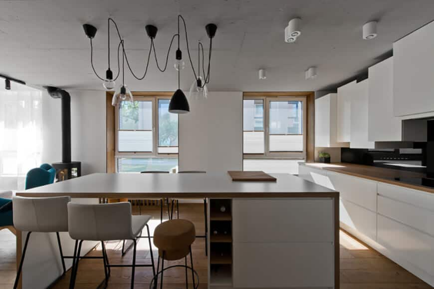 Modern kitchen offers sleek white cabinetry and a breakfast island fitted with a single column wine rack illuminated by various styled pendant lights.