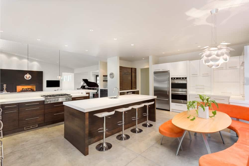 Modern kitchen with white cabinetry beautifully contrasted with a dark wood island bar lined with chrome stools. It includes a bright orange curve chair surrounding a light wood dining table topped with a plant.