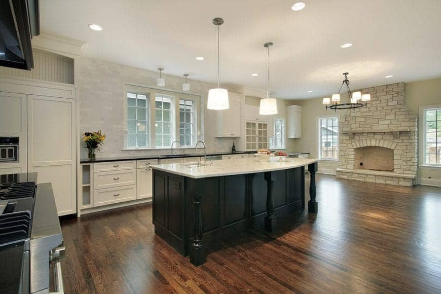 An expansive kitchen with a black breakfast island surrounded with glass windows and white cabinetry along with a stone brick fireplace lighted by a wrought iron chandelier.