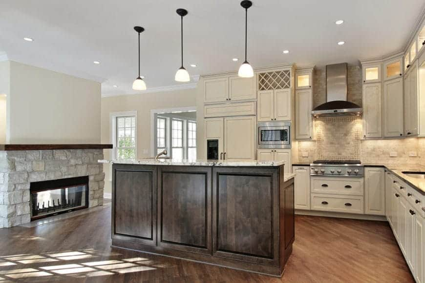 Glass dome pendants illuminate this kitchen offering a two-tier kitchen island and natural stone brick fireplace lined with a wooden mantel.