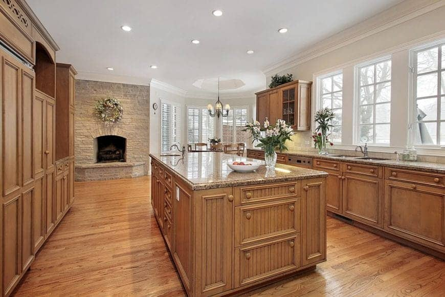 Spacious dine-in kitchen features wood cabinetry and beadboard breakfast island over hardwood flooring with the same tone color creating a unified look.